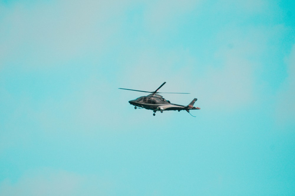 white and black helicopter flying in the sky