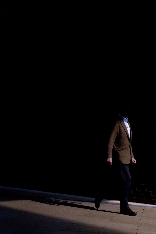 man in brown jacket and black pants
