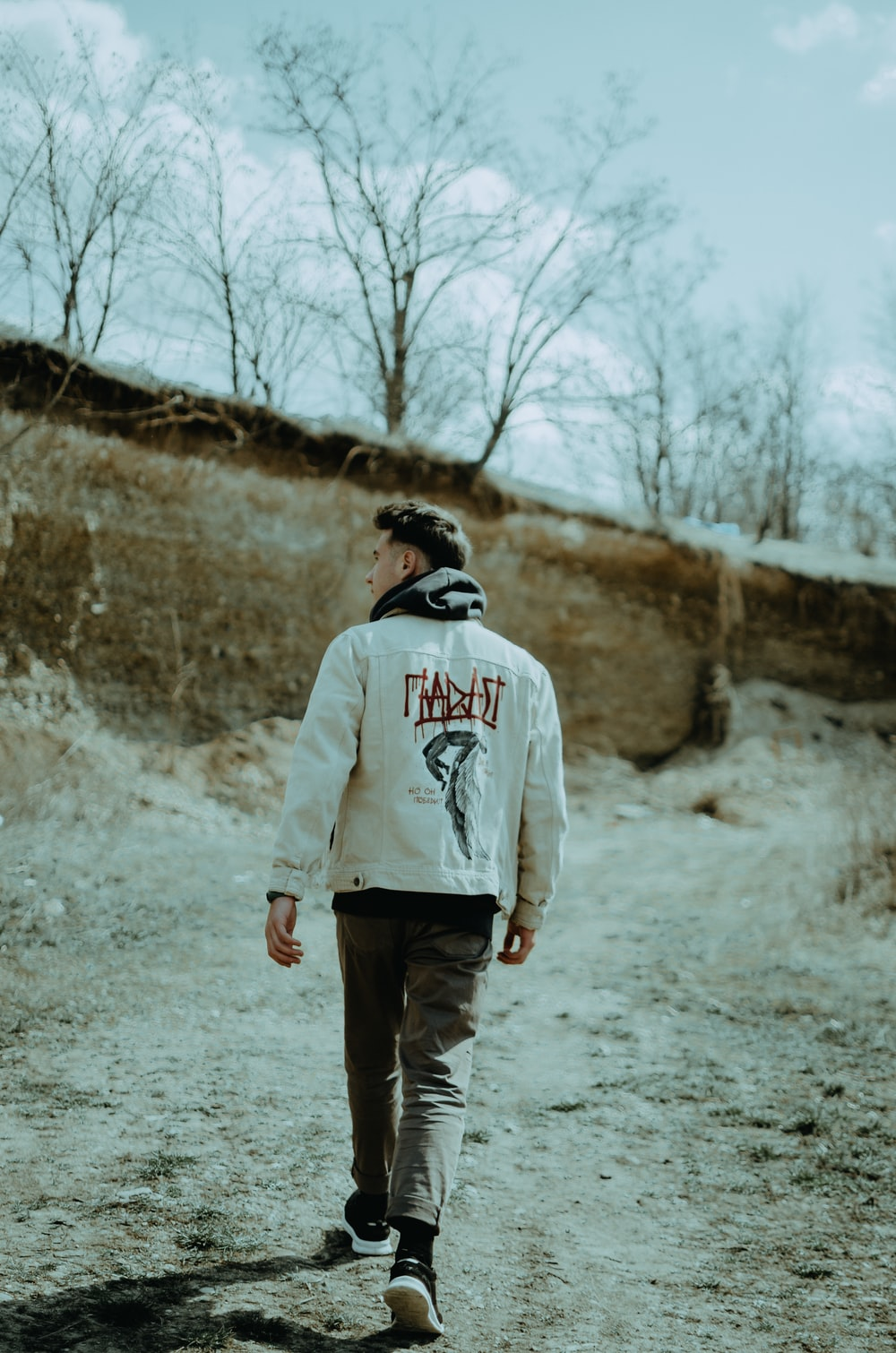 man in gray hoodie standing on gray dirt road during daytime