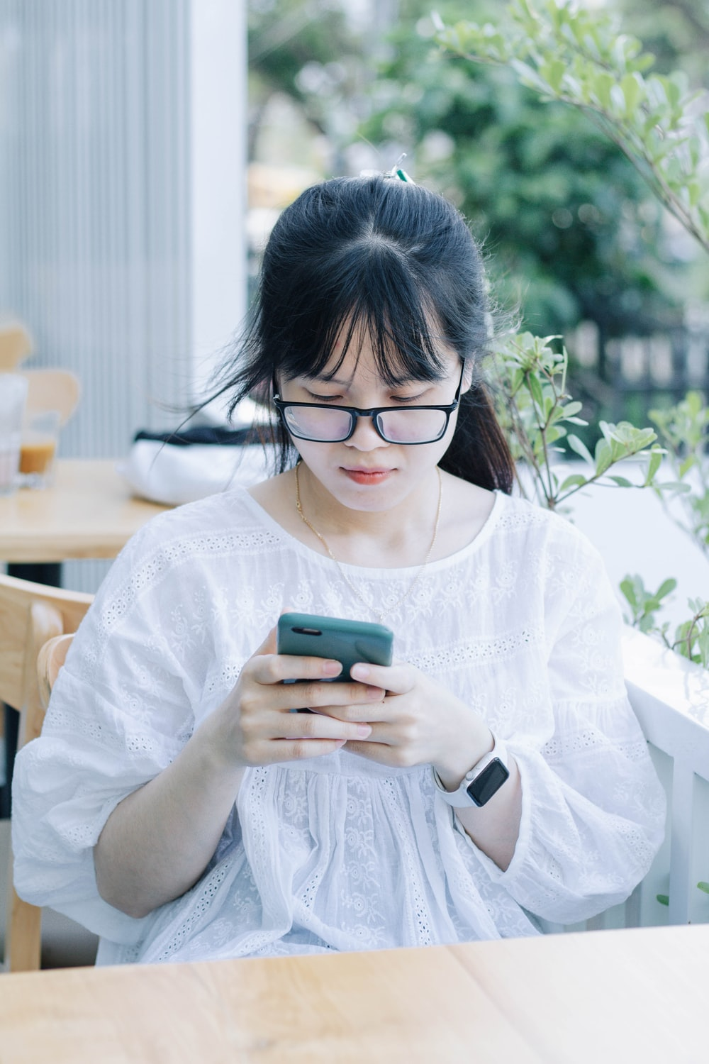 woman in white button up shirt holding green smartphone