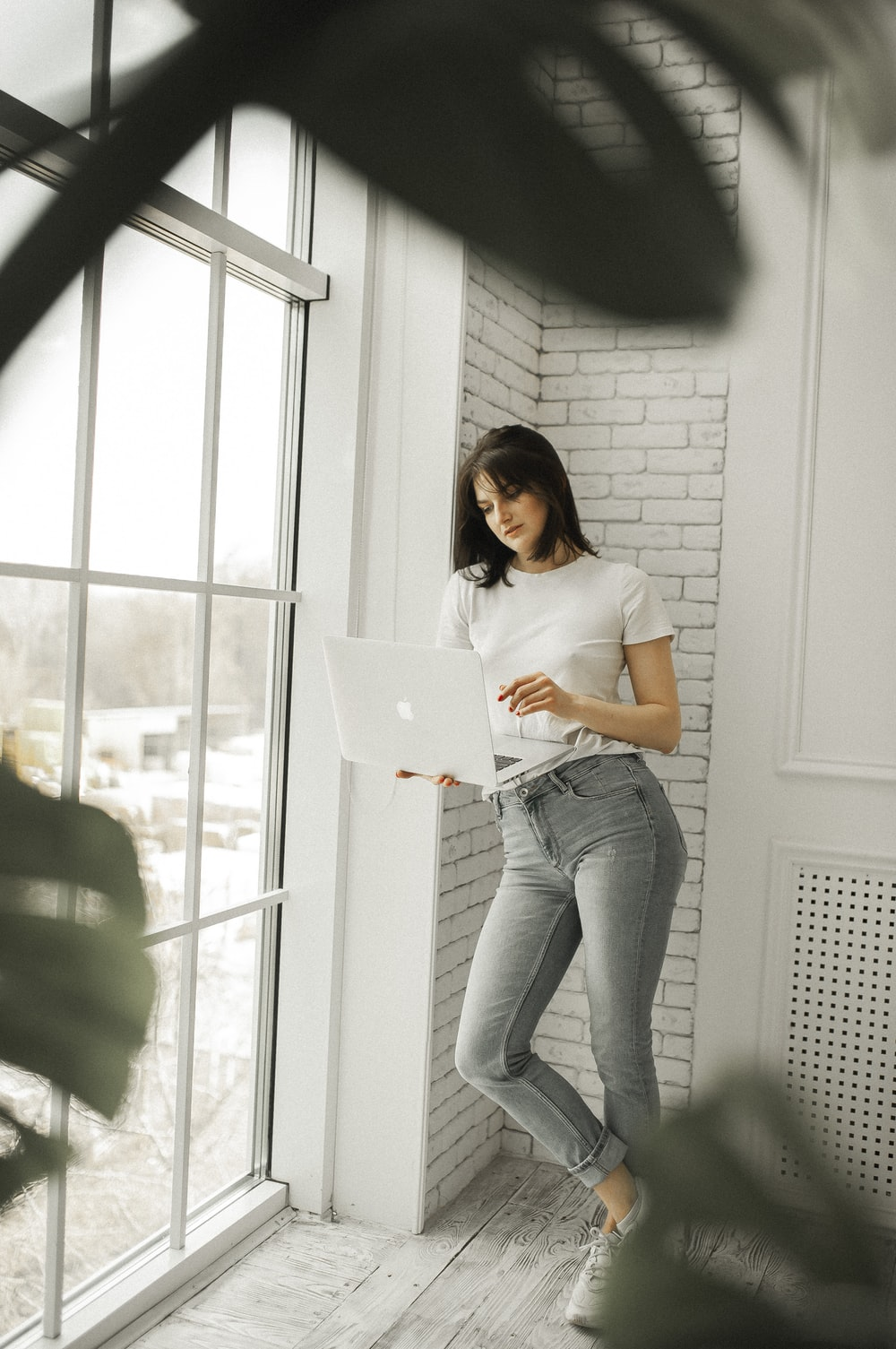 woman in white shirt and blue denim jeans holding white laptop computer