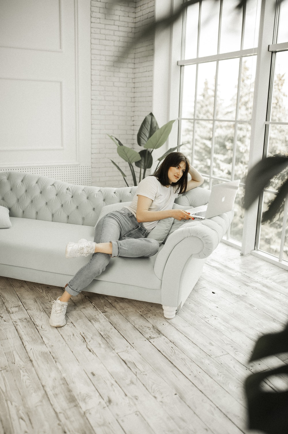 woman in white shirt and blue denim jeans sitting on white couch