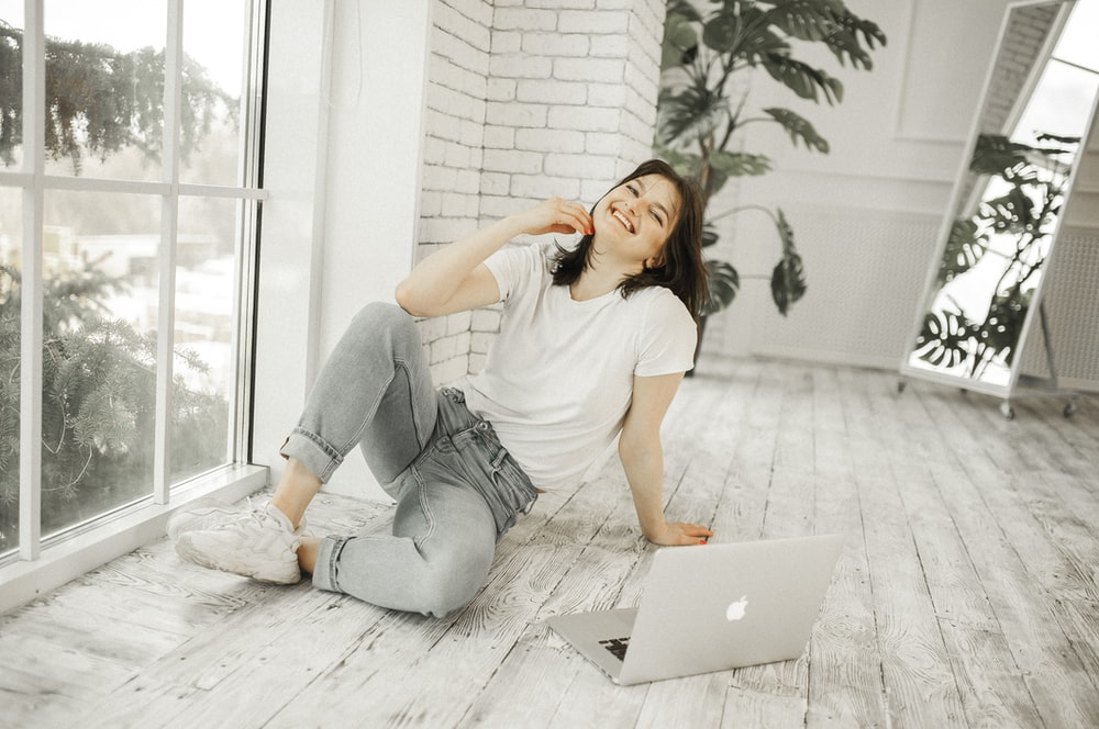 woman in white shirt and blue denim jeans sitting on floor using macbook