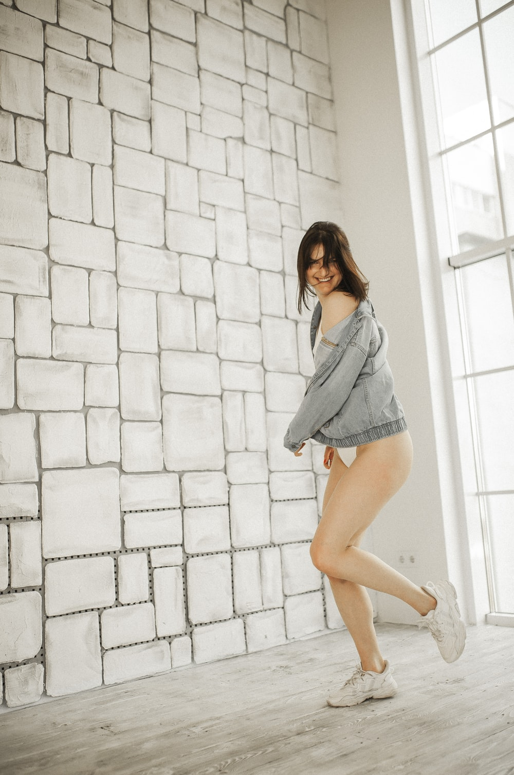 woman in gray long sleeve shirt and blue denim shorts standing beside white brick wall