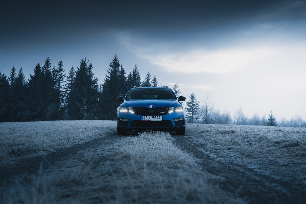 blue car on snow covered field during daytime