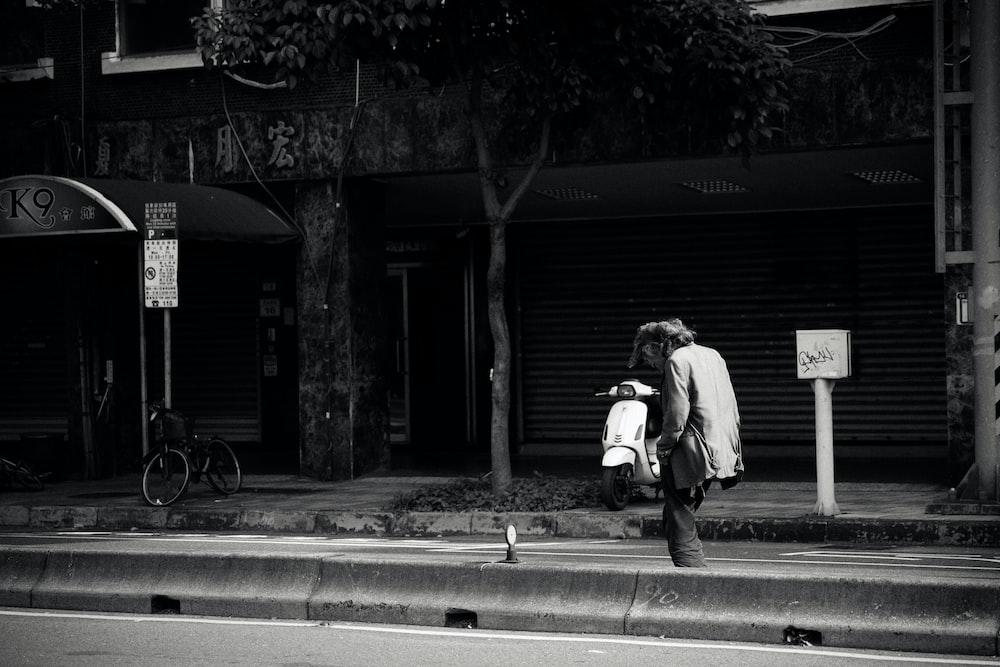 woman in white coat walking on sidewalk near building