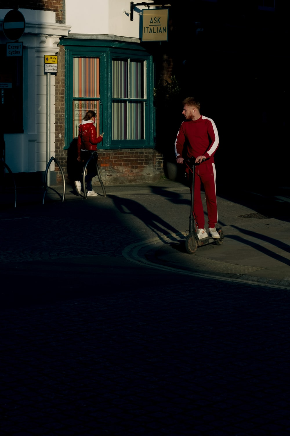 man in red shirt and pants walking with dog during daytime