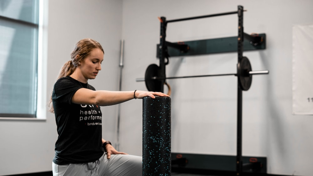 woman in black crew neck t-shirt and gray pants sitting on black exercise equipment