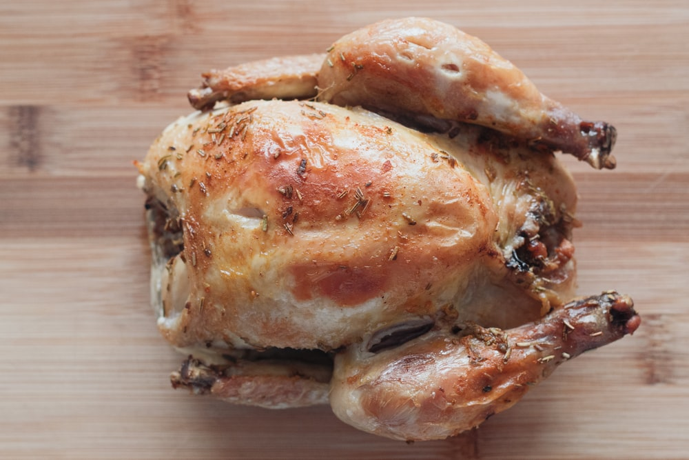roasted chicken on brown wooden chopping board