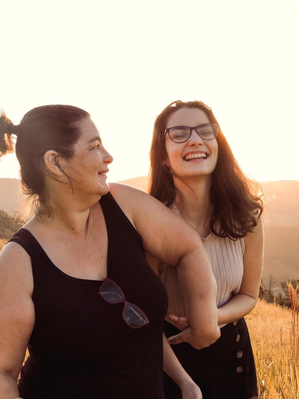woman in black tank top beside woman in white tank top