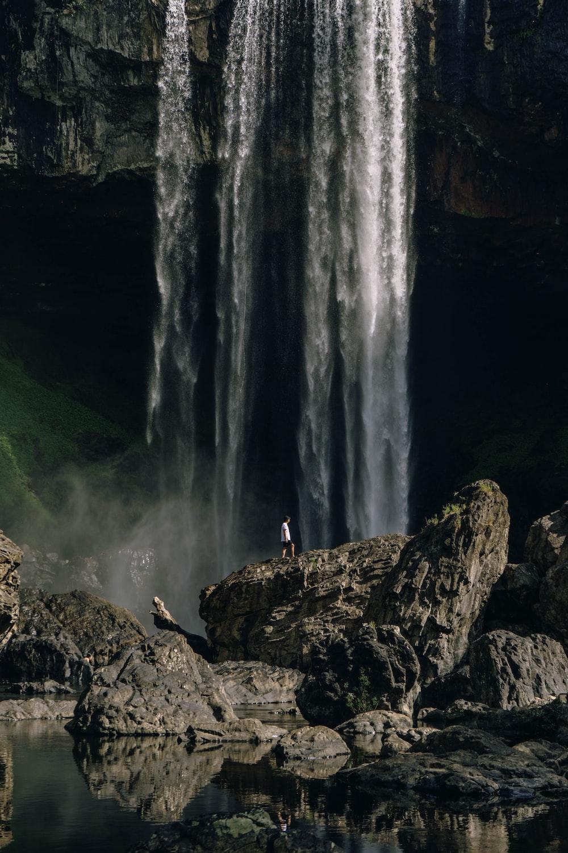 man standing on rock near waterfalls during daytime
