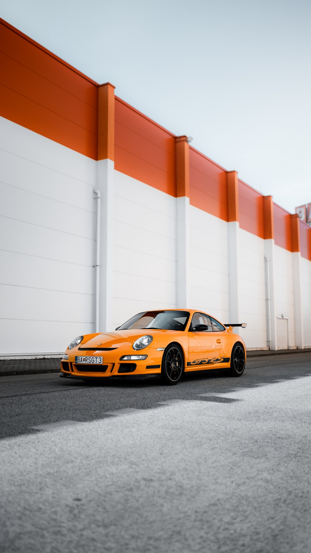 orange and black porsche 911 parked beside white and red wall