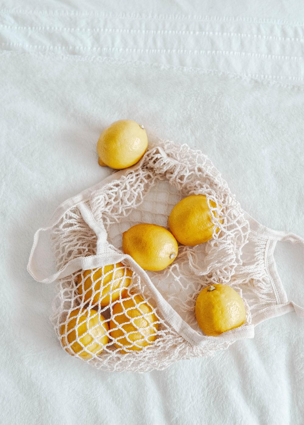 yellow citrus fruit on white lace textile