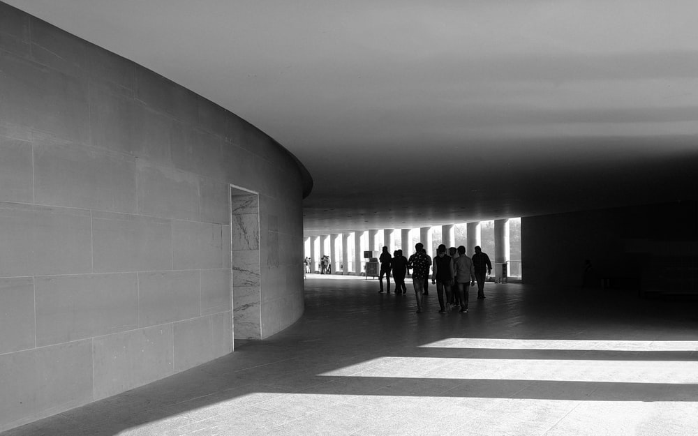 people walking on hallway in grayscale photography