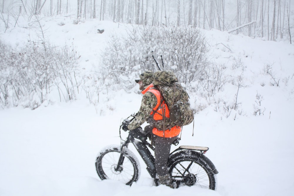 woman in brown jacket riding on black motorcycle on snow covered ground during daytime