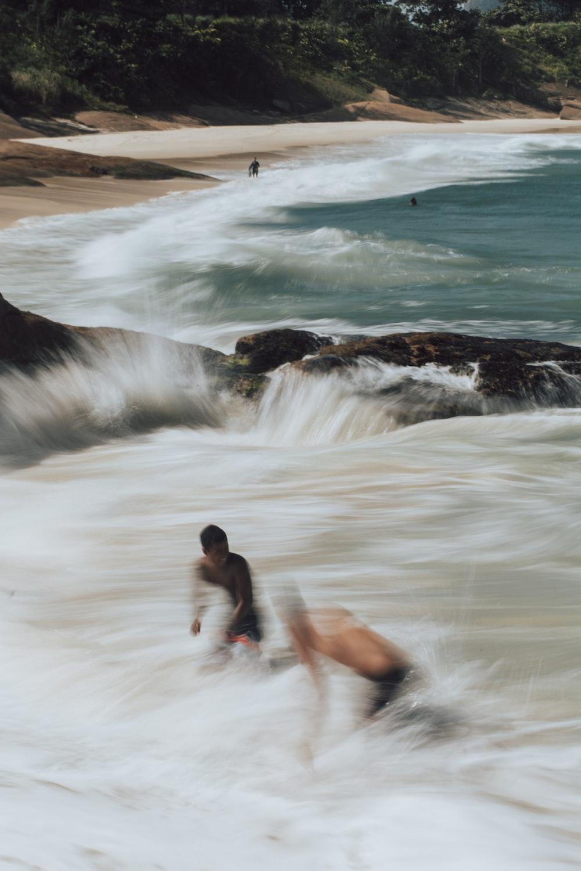 man in black shorts sitting on brown rock near ocean waves during daytime