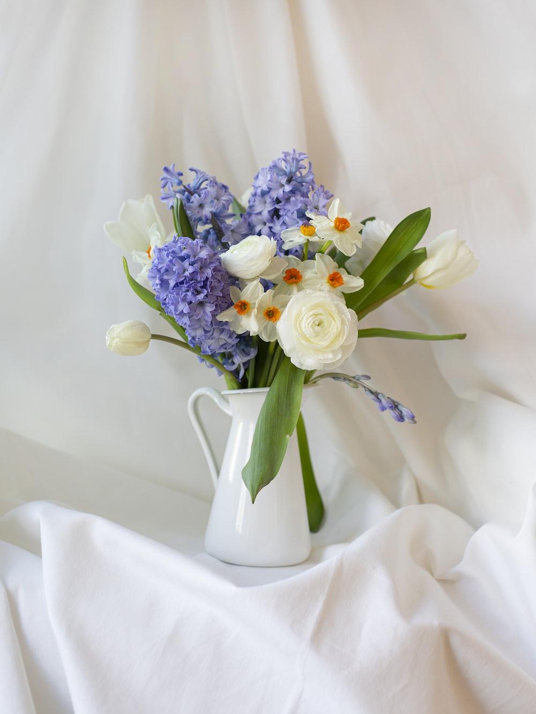 white and purple flower bouquet in white ceramic vase