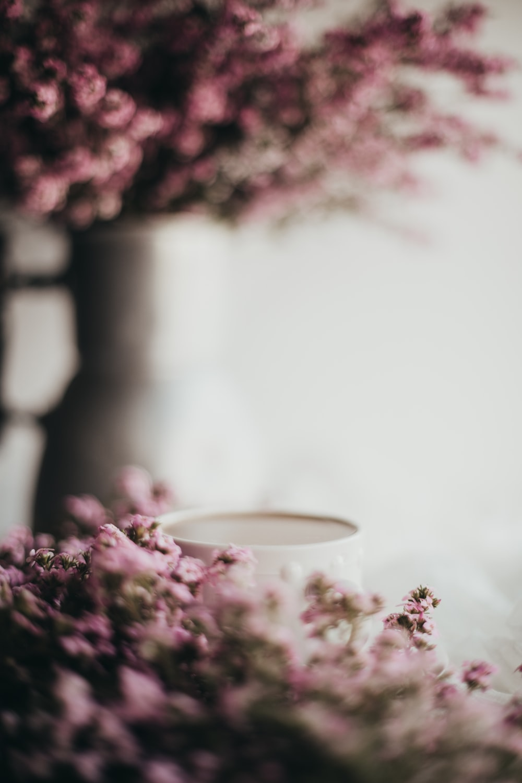 purple flowers beside white ceramic mug