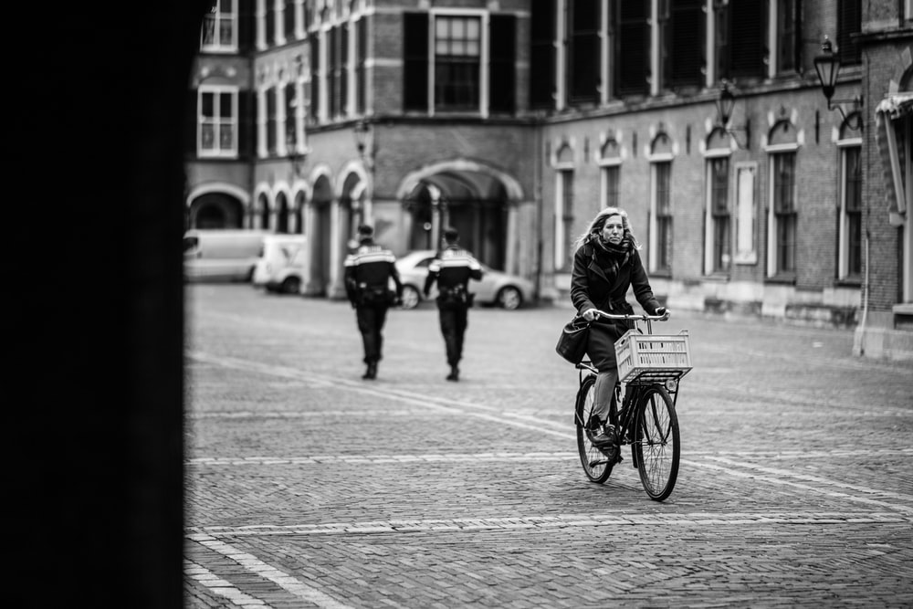 grayscale photo of woman riding bicycle on road