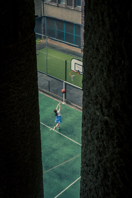 boy in green shirt playing soccer during daytime