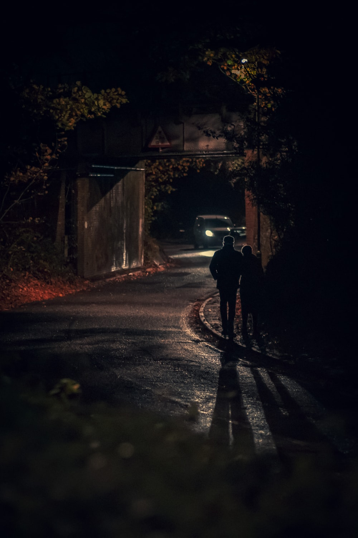 man in black jacket walking on the street during night time