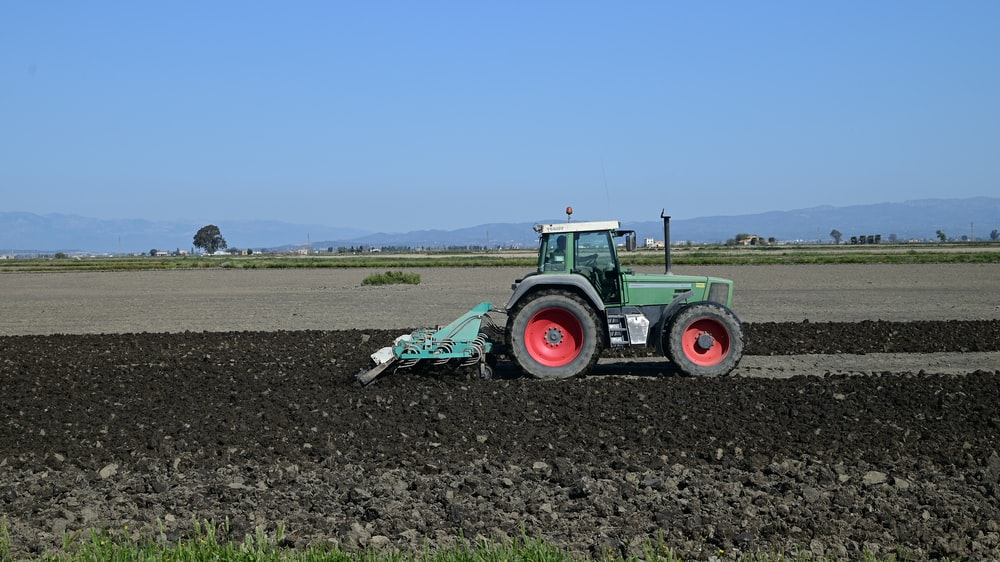 green tractor on brown field under blue sky during daytime