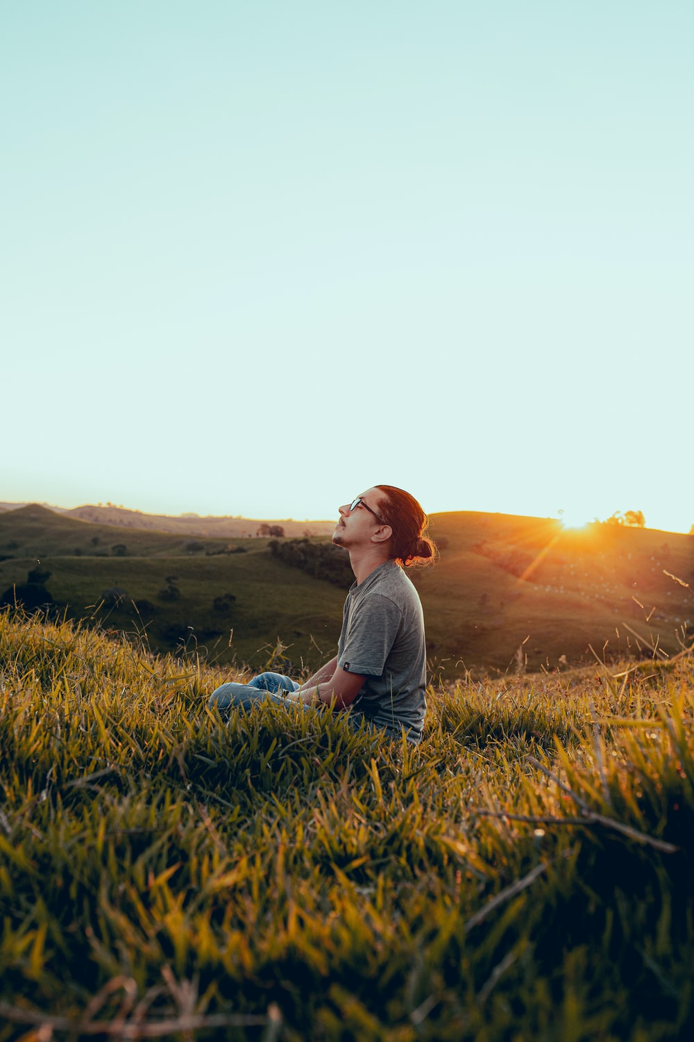 man in white shirt sitting on green grass field during sunset