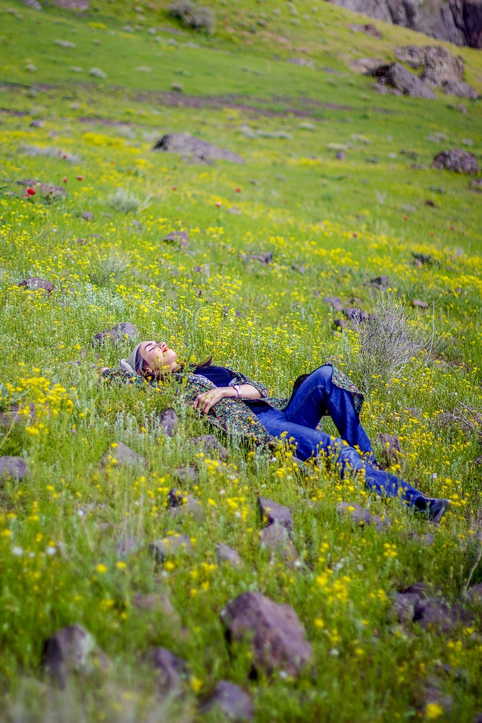 man in black jacket lying on blue blanket on green grass field during daytime