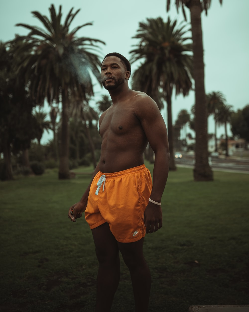 topless man in orange shorts standing on green grass field during daytime