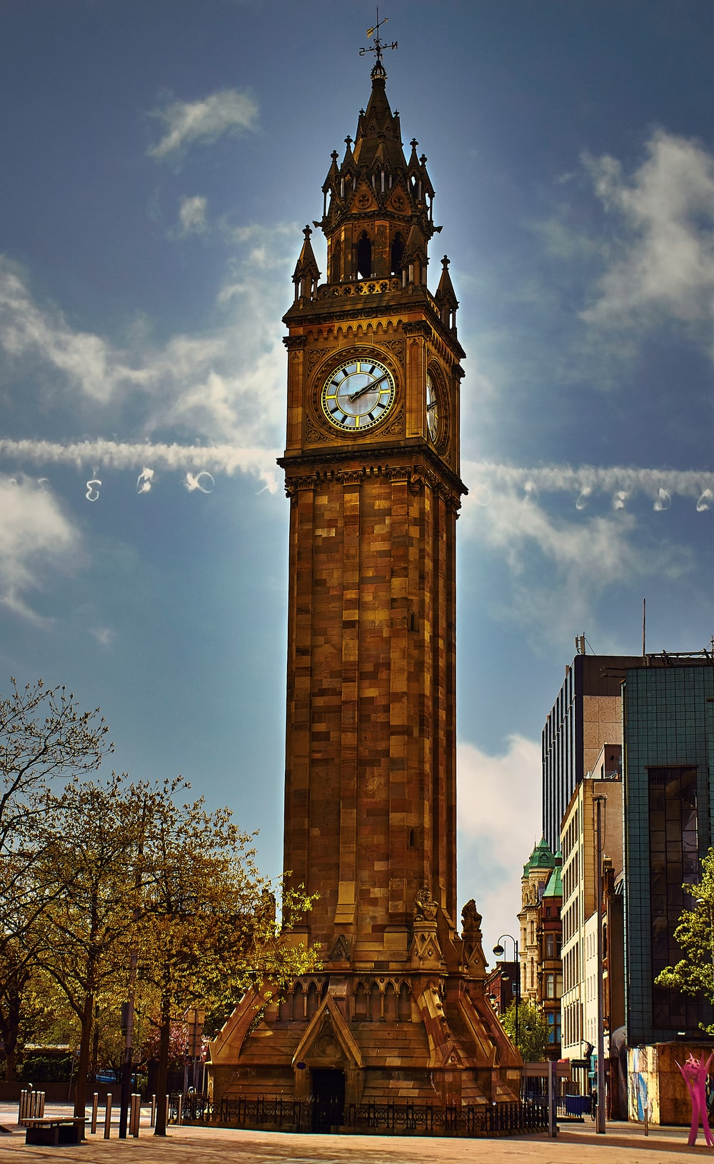 brown tower clock under cloudy sky during daytime