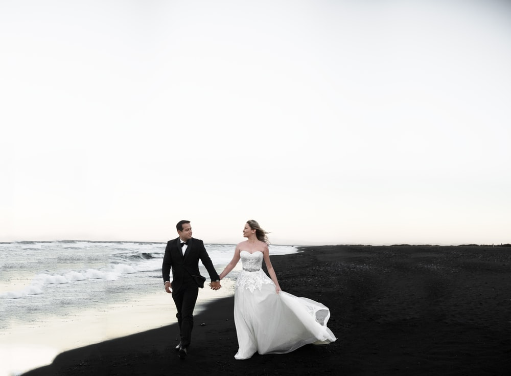 bride and groom walking on beach during daytime