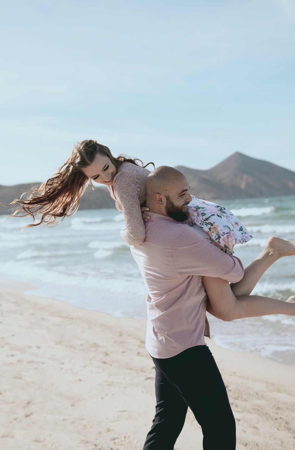 man and woman kissing on beach during daytime