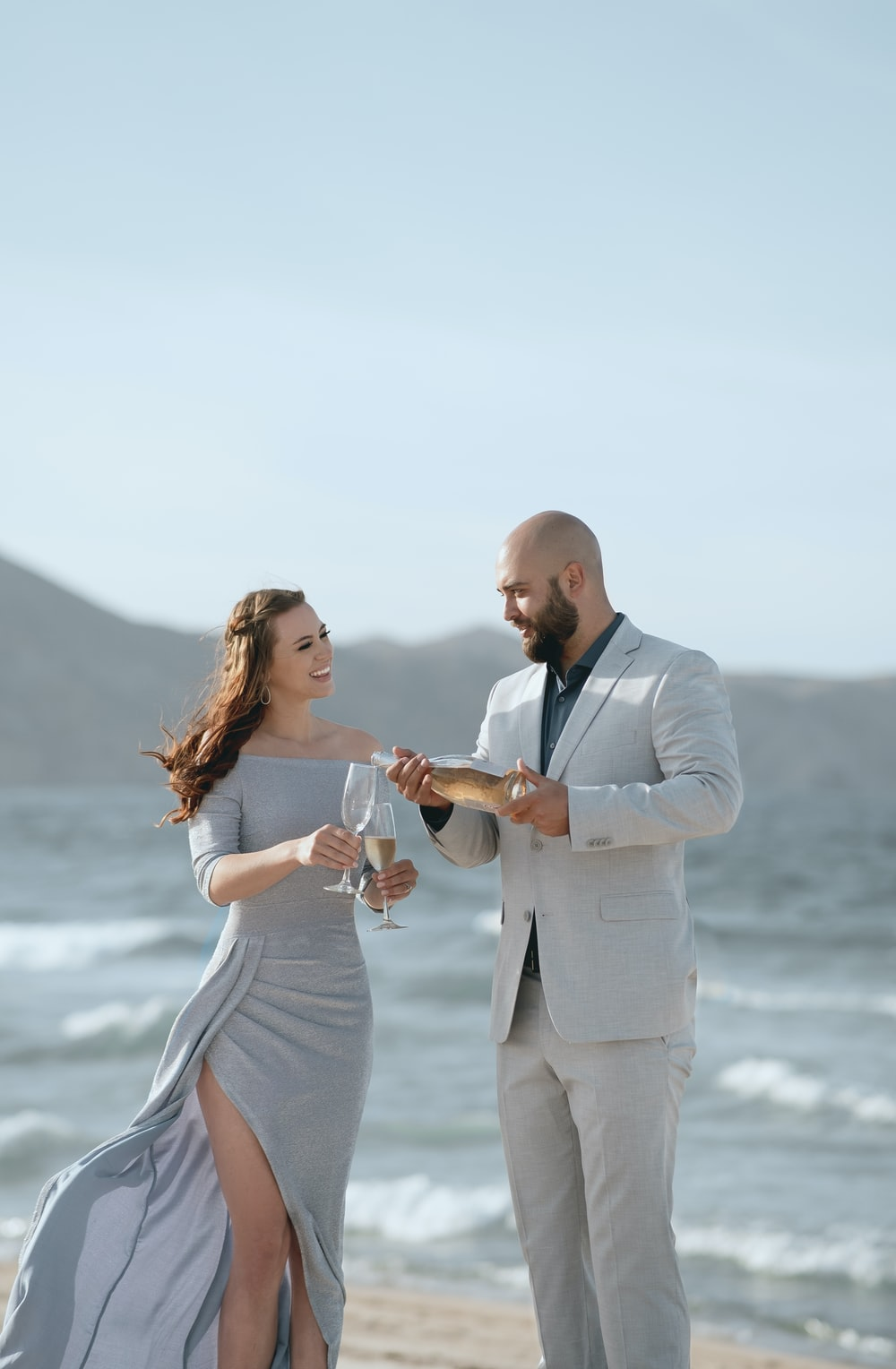 man in black suit jacket holding woman in white dress