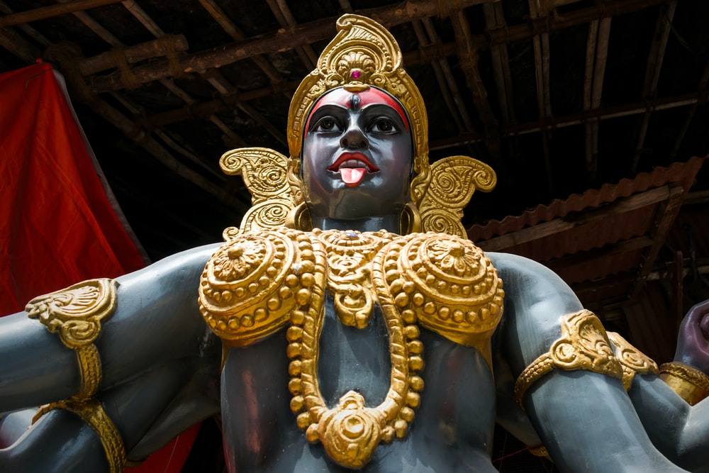 gold hindu deity statue in a room