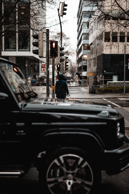 man in black jacket standing beside black car during daytime