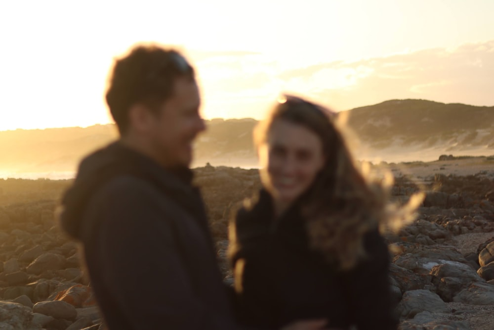 man and woman standing near body of water during sunset
