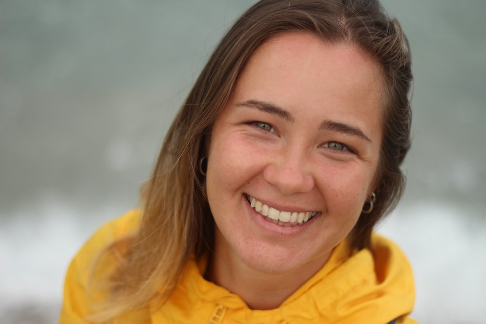 woman in yellow collared shirt smiling