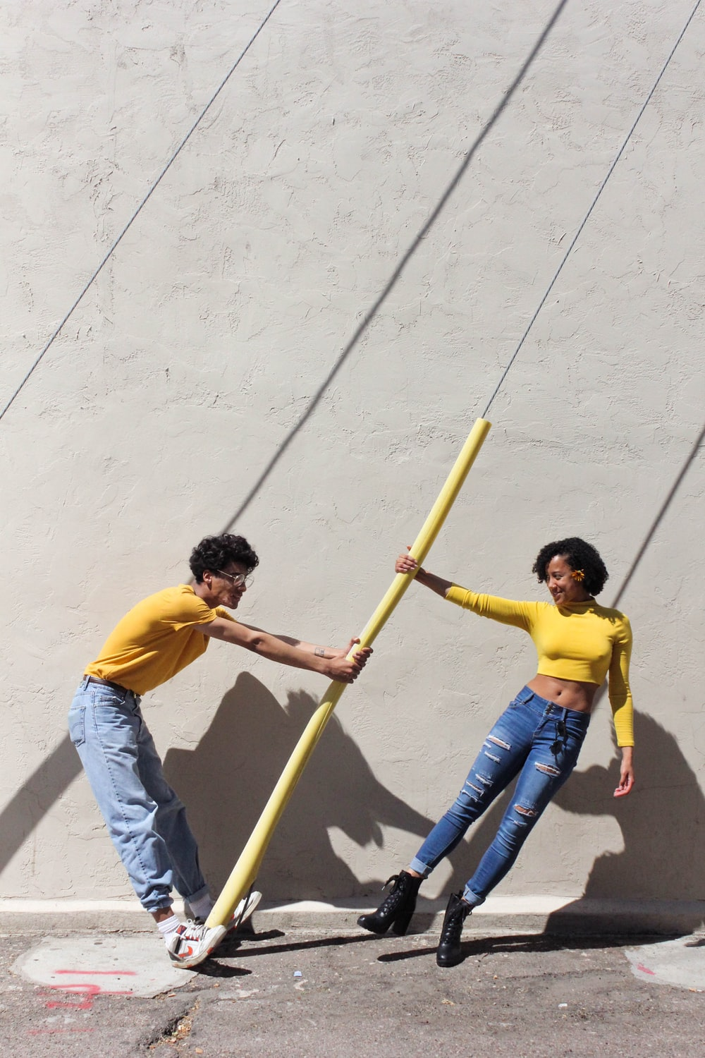 man in yellow shirt and blue denim jeans holding brown wooden stick