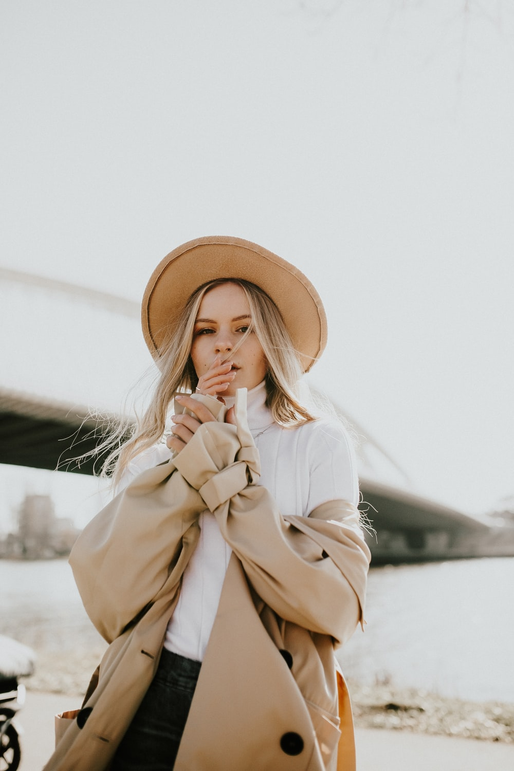 woman in brown sun hat and white coat
