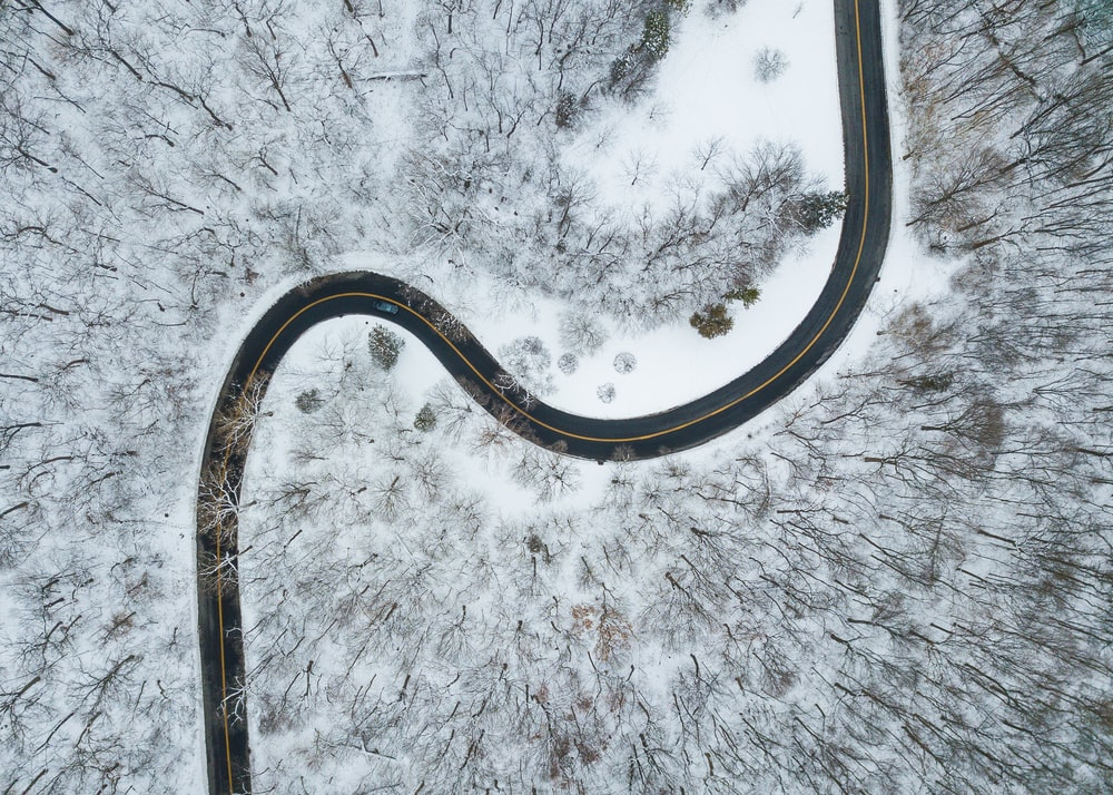 aerial view of road in the middle of snow covered trees