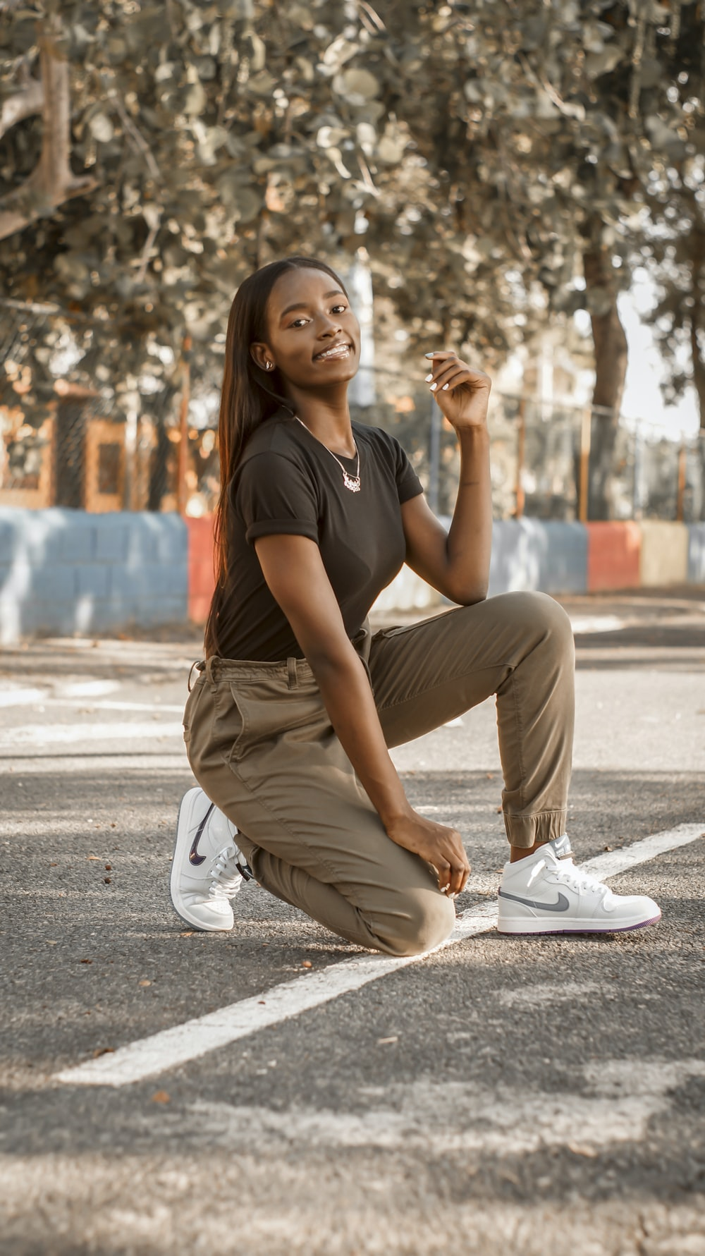 woman in black t-shirt and brown pants sitting on concrete floor during daytime