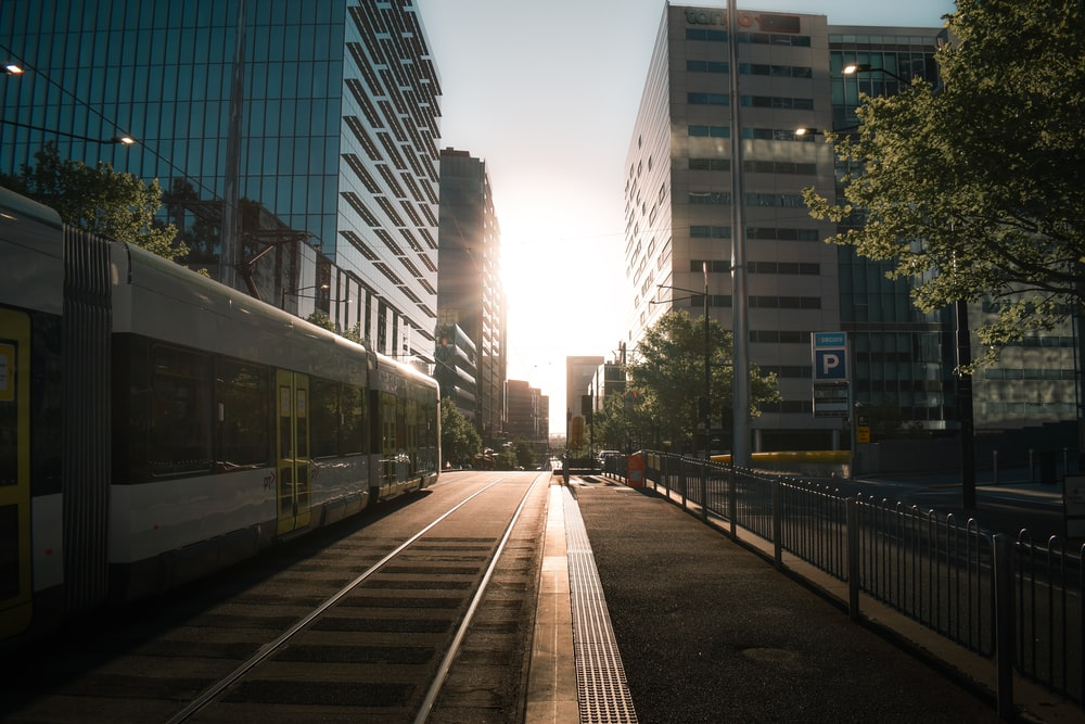 white train on rail road near high rise buildings during daytime