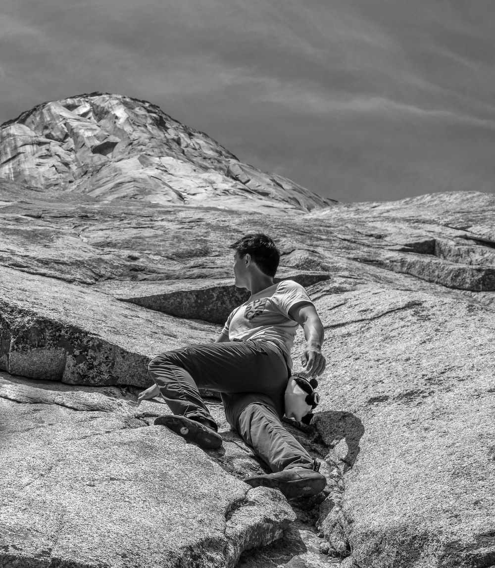 grayscale photo of woman in tank top and pants sitting on rock