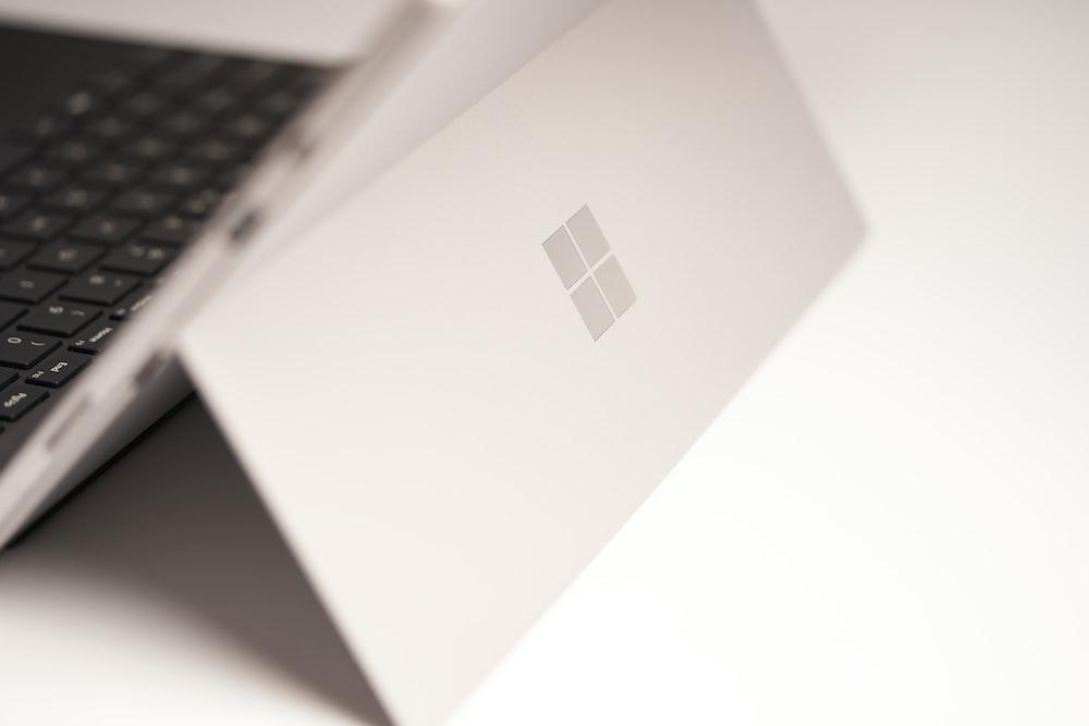 white laptop computer on white table
