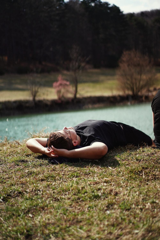 woman in black shirt lying on green grass field