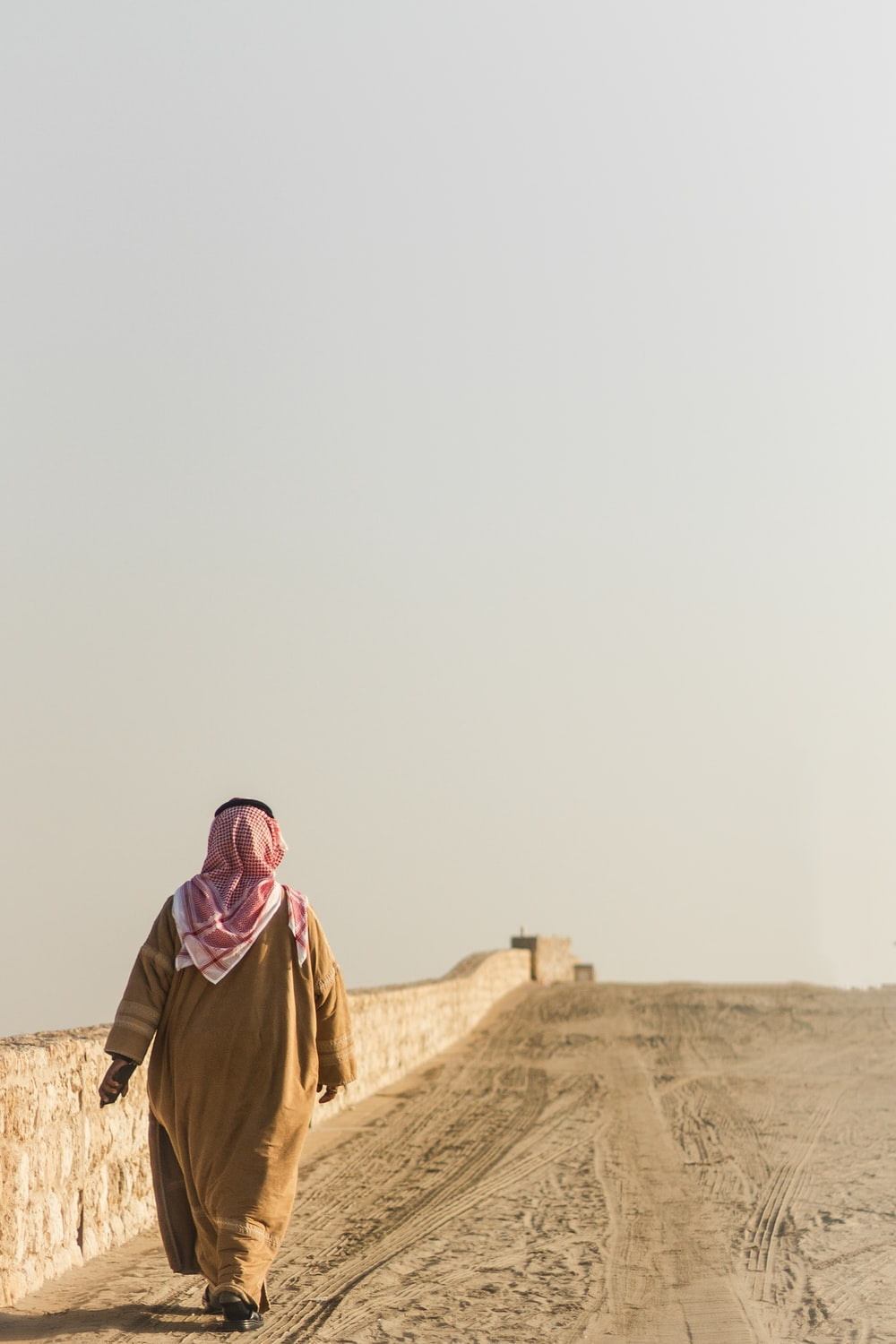 woman in brown hijab standing on brown sand during daytime
