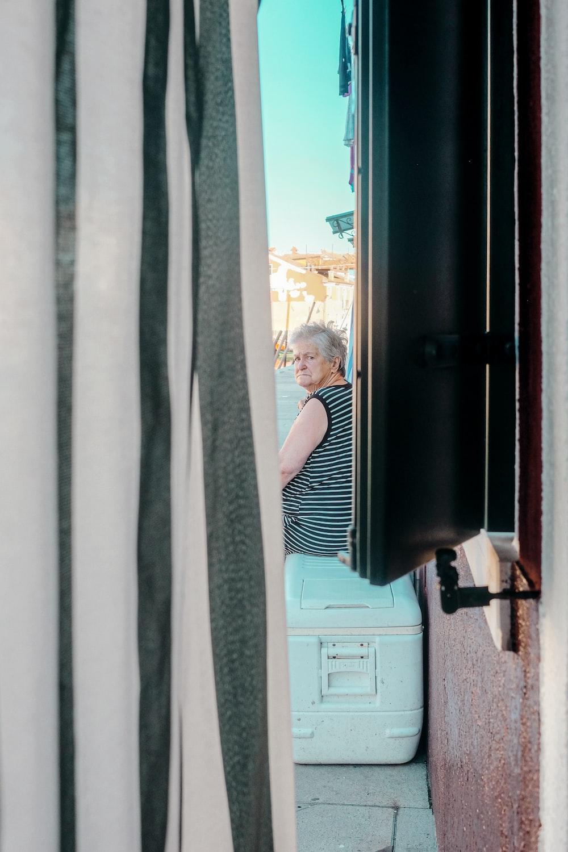 woman in black and white stripe dress standing beside window