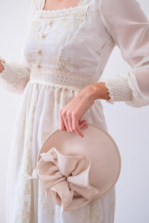 woman in white long sleeve dress holding white heart pillow