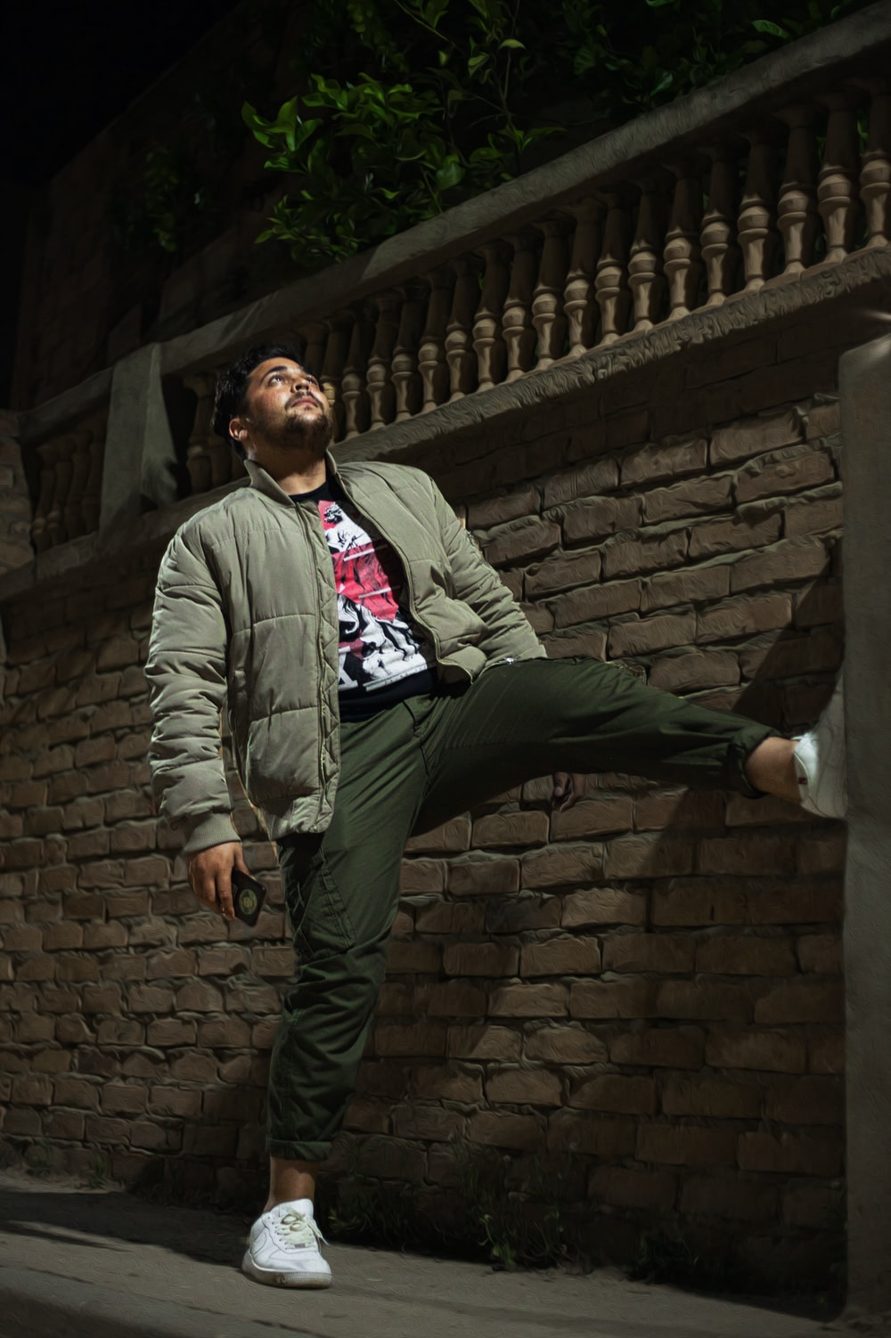 man in gray jacket standing beside brick wall
