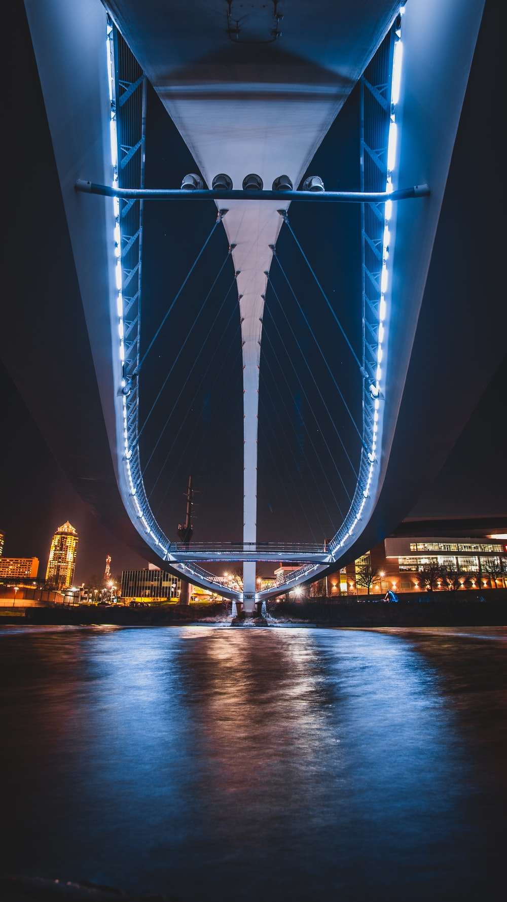 blue bridge over body of water during night time